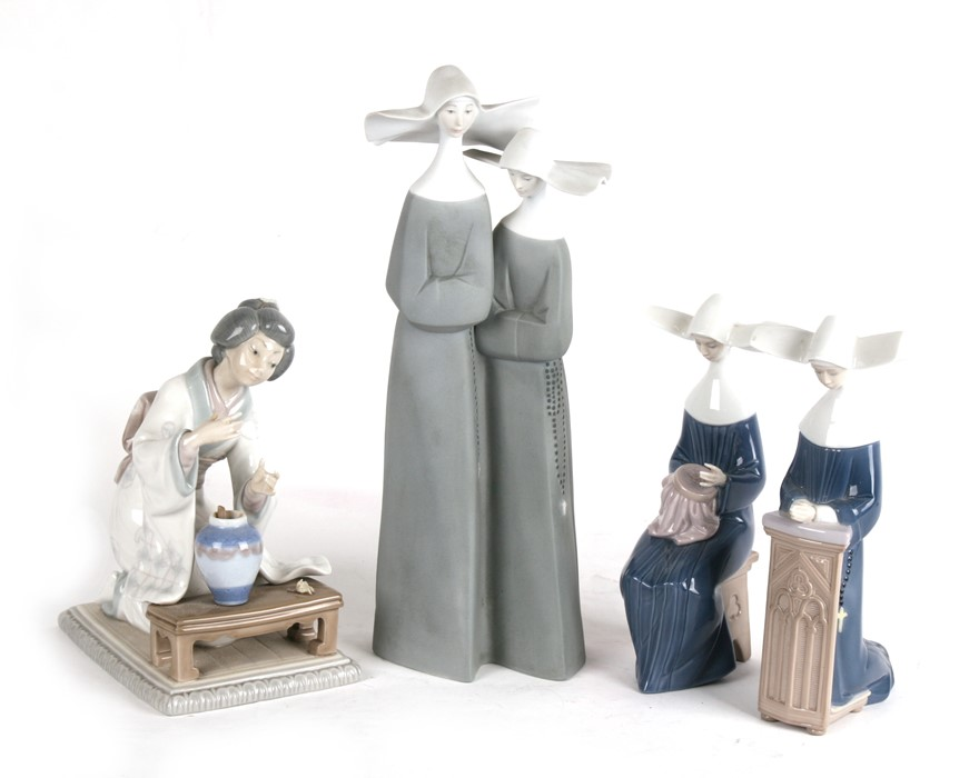 Lot 88 - A Lladro group depicting two nuns, 33cms (13ins) high; together with two similar smaller and another