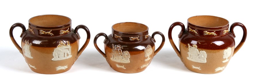 Lot 33 - Three Victorian Doulton stoneware two-handled pots decorated with figures and dogs, the largest