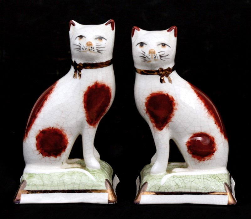 Lot 48 - A pair of Staffordshire ware pottery figures in the form of seated cats, 11cms (4.25ins) high.