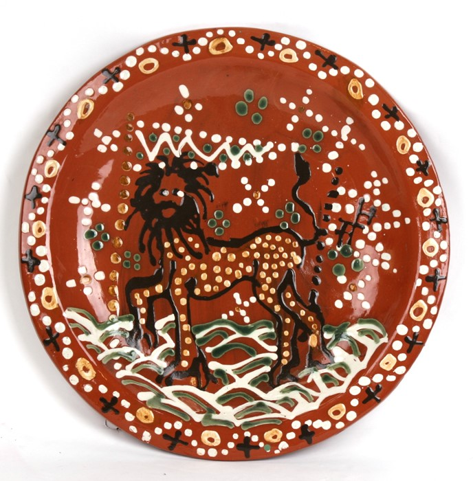 Lot 87 - A slipware charger decorated with a stylised lion, 42cms (16.5ins) diameter.