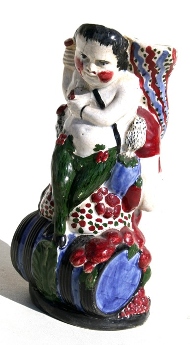 Lot 45 - An early 19th century Prattware vase in the form of a man seated on a barrel holding a cornucopia,