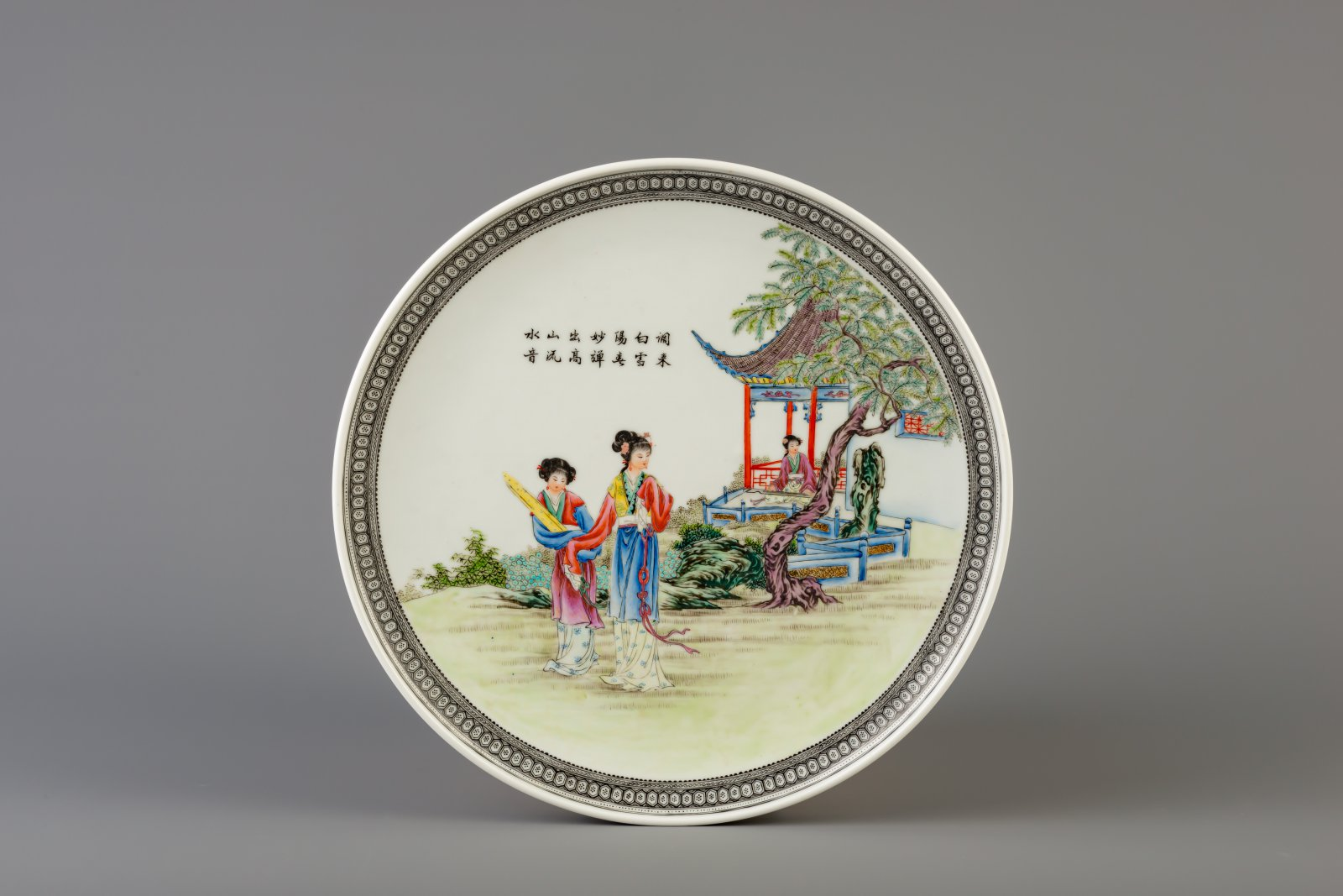 Lot 47 - A Chinese famille rose charger with ladies in a garden, Qianlong mark, 20th C.