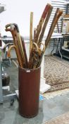 Group of walking sticks, canesand a shooting stickin a leather-bound stand