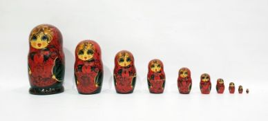 Russian Matryoshka dollpainted in bright colours reserved on a red ground enclosing nine smaller