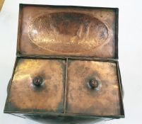 An Arts and Crafts copper hinged rectangular section tea caddy and cover and two liners, with oval