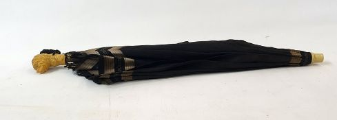 Black and silver fabric parasol with a bakelite handle in the form of a dogs head