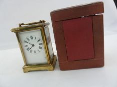 Brass carriage timepiece in plain case, with red leather-bound travelling case, 15cm high