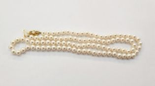 String of cultured pearlswith 18ct gold bow-pattern clasp set with single pearl, 75cm long