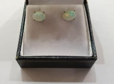 Pair of white metal Ethiopian opal stud earrings, each with oval cabochon stone