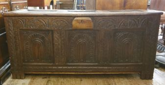18th century oak coffer, the three-panelled top with moulded stiles, lunette carved front, with