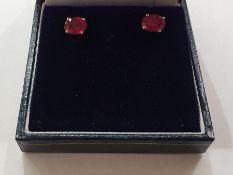 Pair of white metal heat-treated ruby stud earrings, each set oval cut stone