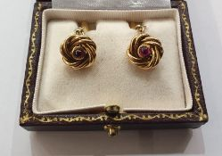 Pair gold-coloured knot, torpedo and chain cufflinks, each knot set with single cabochon ruby,