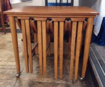 Teak coffee table with four folding coffee tables slung under, the whole on casters