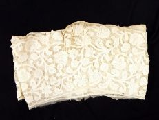 Early handmade tape-lace backed onto muslin, featuring floral decoration, possibly cut from a