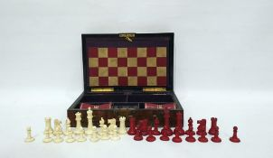 Figured walnut and brass-bound games box, rounded oblong and fitted with bone chess pieces, counters
