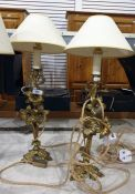 Pair of brass table lamps, each decorated with three flowerheads and leaves on a foliate tripod