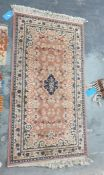 Modern peach ground rug with central medallion foliate decorated field and stepped border, 156cm x