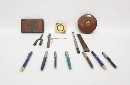 Assorted itemsto include pens, a South African 1900 Queen Victoria tin box, thermometer, clock, etc