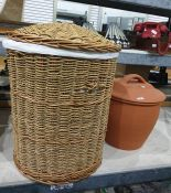 One wicker laundry basket containing a blue throw and large earthenware covered pot