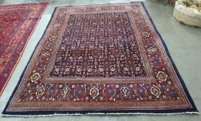 Blue ground rugwith allover foliate decoration, on a stepped border, 224cm x 315cm
