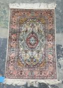 Two Eastern rugs, one white ground with central pink ground stepped foliate medallion, foliate