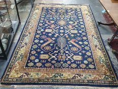 Blue ground rug, the central field with flowerhead and hooked motifs, stepped border, 239cm x 155cm