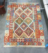 Cream ground rug with blue, green and red diamond pattern to central field on stepped border 140