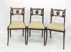 Set of four Regency simulated rosewood dining chairswith anthemion and scroll carved backs, gold