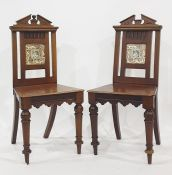 Pair of 19th century mahogany hall chairs with broken arch top rails, the back splats featuring