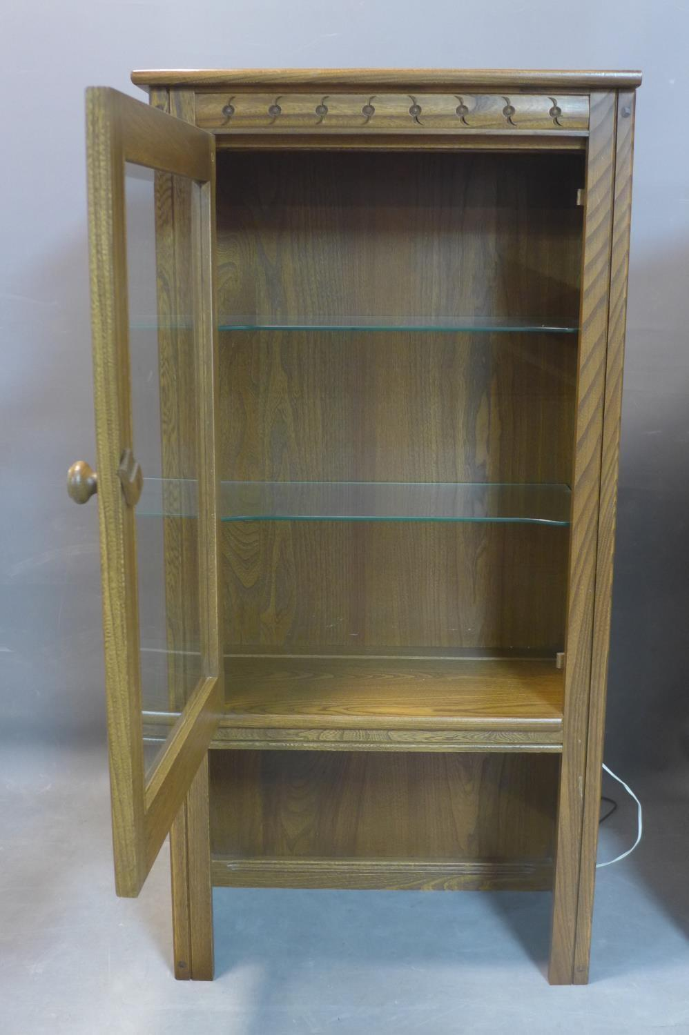 Lot 181 - A pair of mid century Ercol teak cabinets, having bevelled glass glazed doors, bearing label, H.