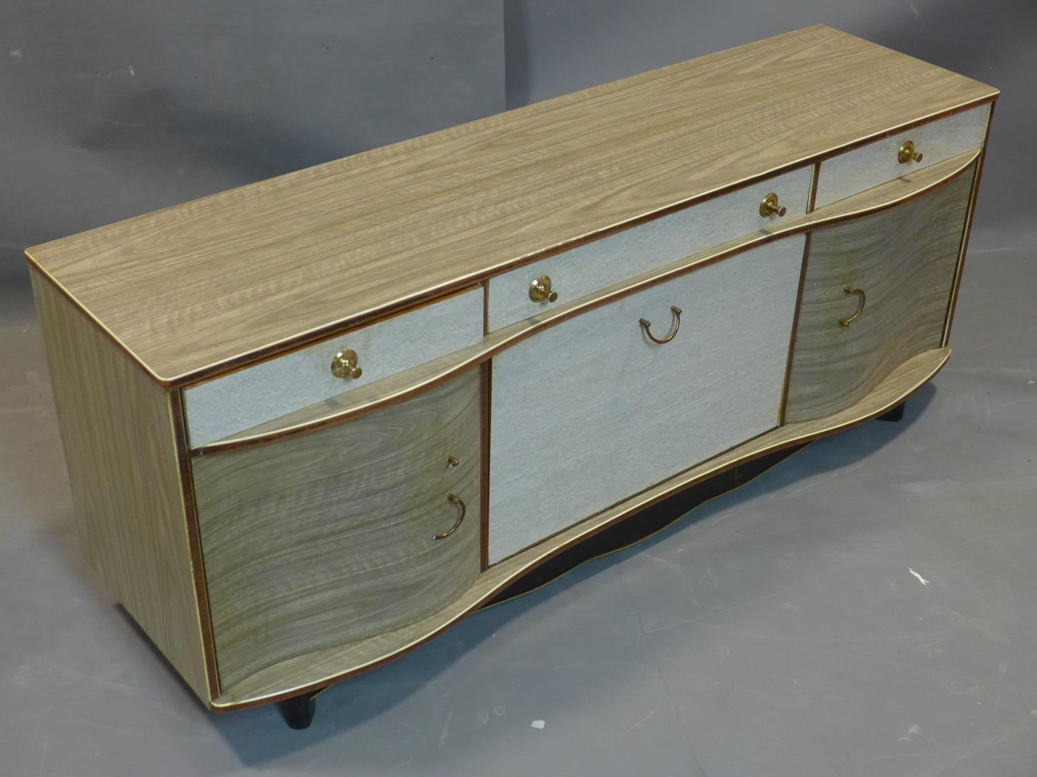 Lot 12 - A 1960's serpentine fronted sideboard, with one long and two short drawers, above central drinks