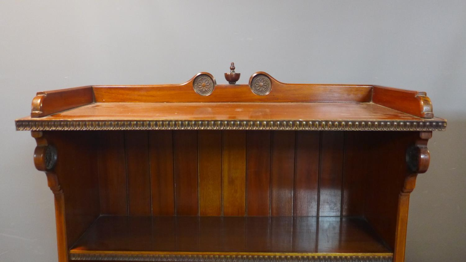 Lot 247 - A pair of Victorian walnut open waterfall bookcases with egg and dart edges, having floral carving