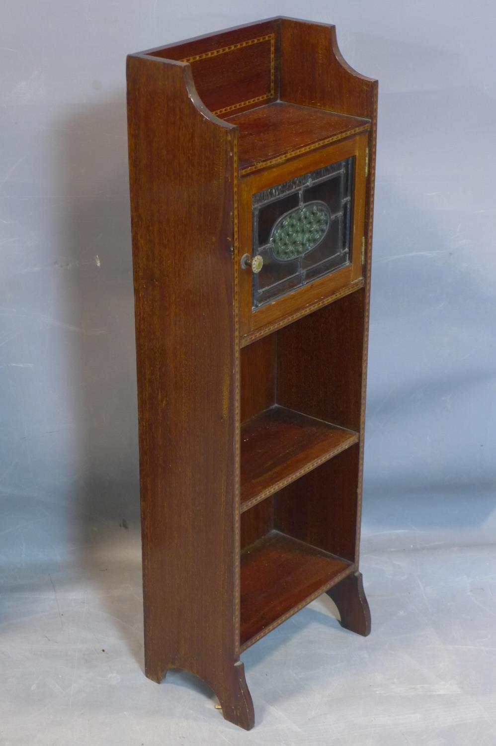 Lot 249 - A small Arts and Crafts mahogany and inlaid narrow side cabinet, with single leaded glass door above