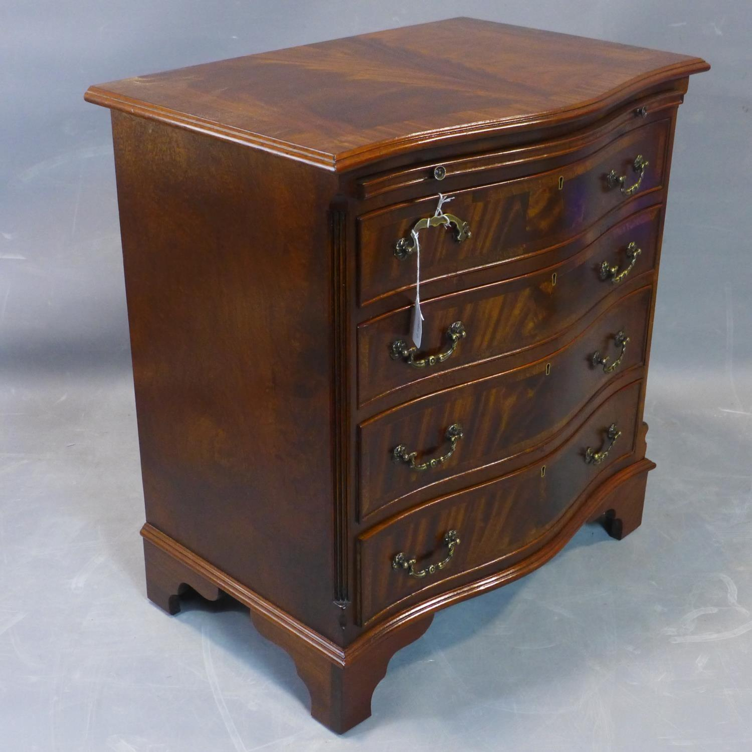 Lot 279 - A serpertine fronted figured mahogany Bachelor's chest, with cross-banded top above brush slide