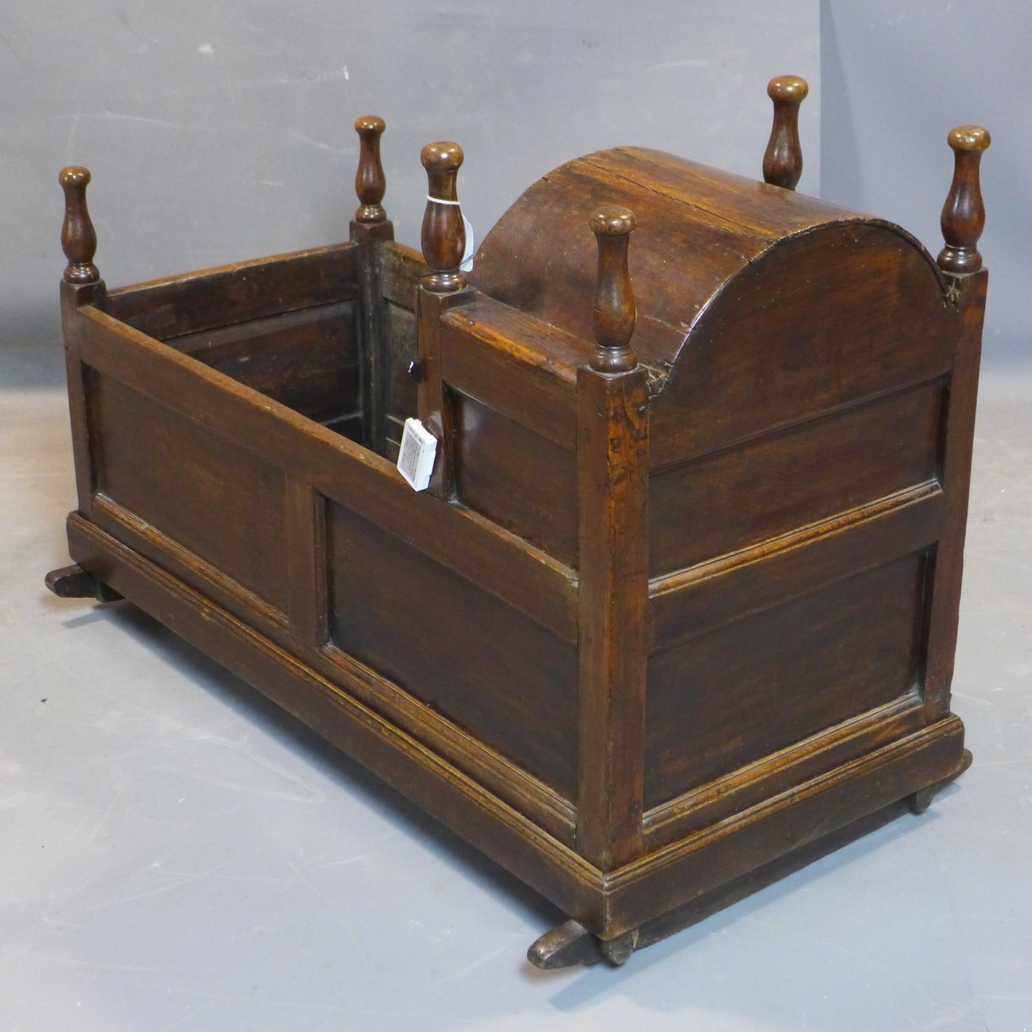 Lot 23 - An 18th century oak cradle, with turned finials and panelled sides, H.75 W.104 D.60cm