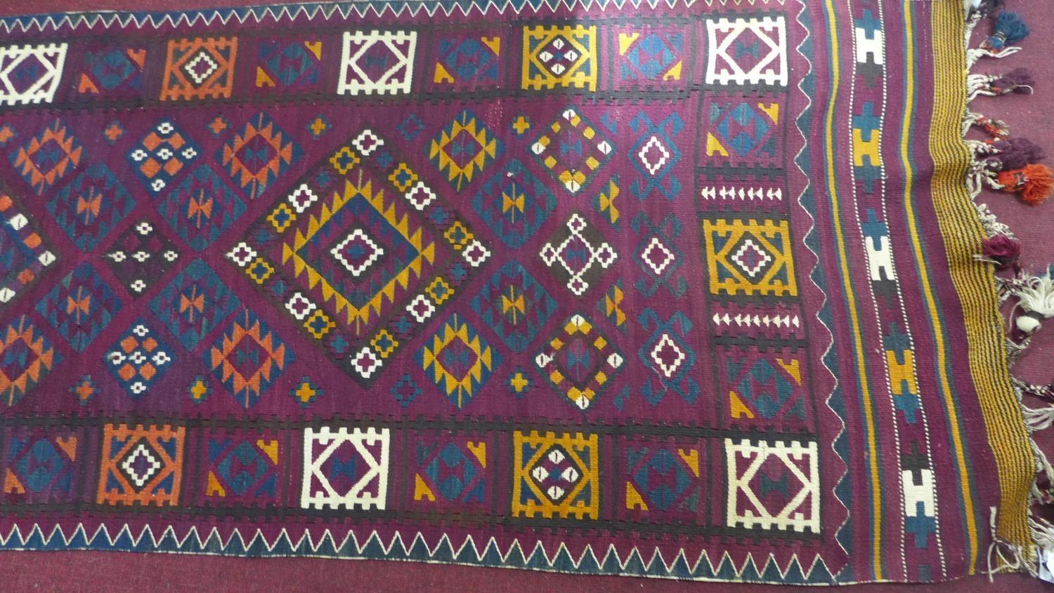 Lot 72 - An Afghan Belouch kelim, with three diamond medallions and geometric motifs on a purple ground,