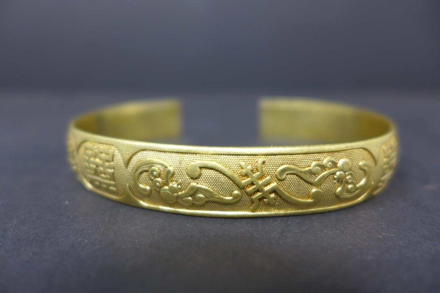 Lot 265 - A Chinese silver gilt bangle, decorated with phoenixes, scrolling foliage and Chinese symbols,