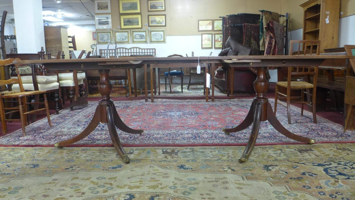 Lot 153 - A Regency style mahogany extending D-end dining table, with extra leaf, having two pedestals, raised