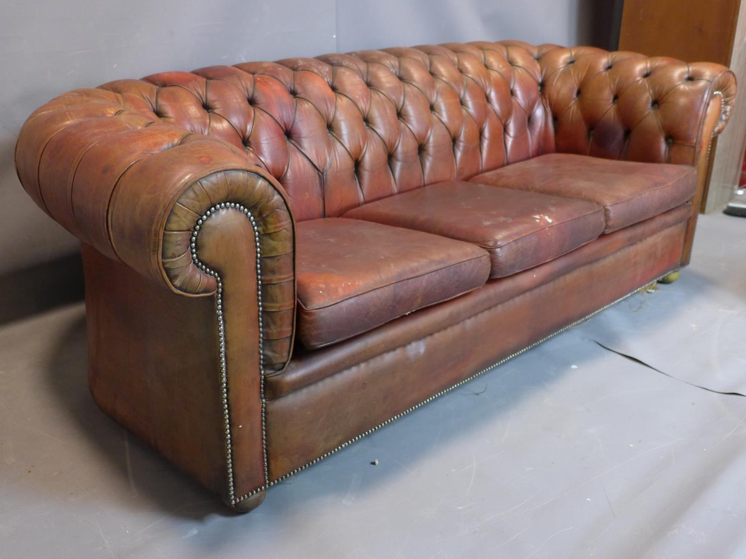 Lot 26 - A three seater leather Chesterfield sofa, with button back upholstery, heavily worn