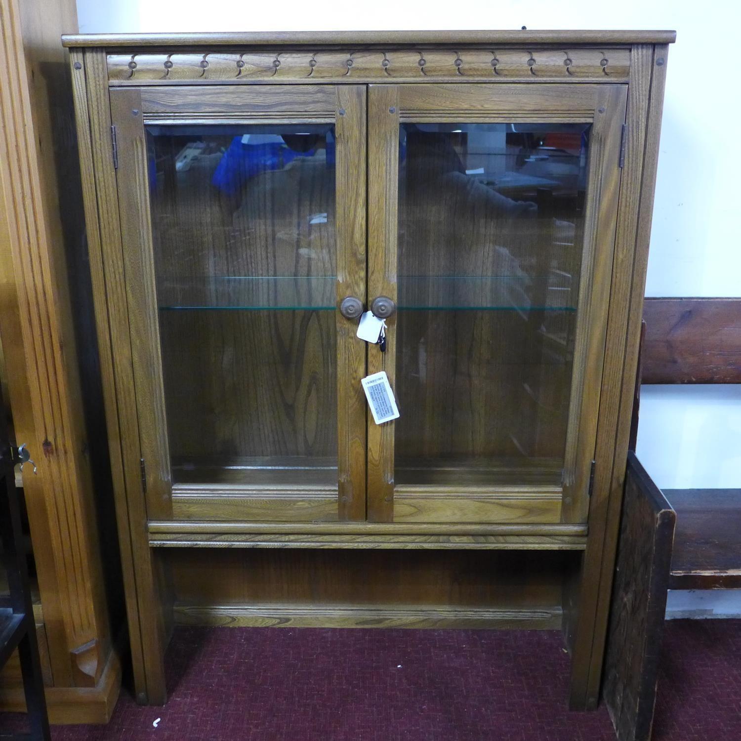 Lot 180 - A mid century Ercol teak cabinet, with two glazed doors, label to verso, H.126 W.93 D.33cm