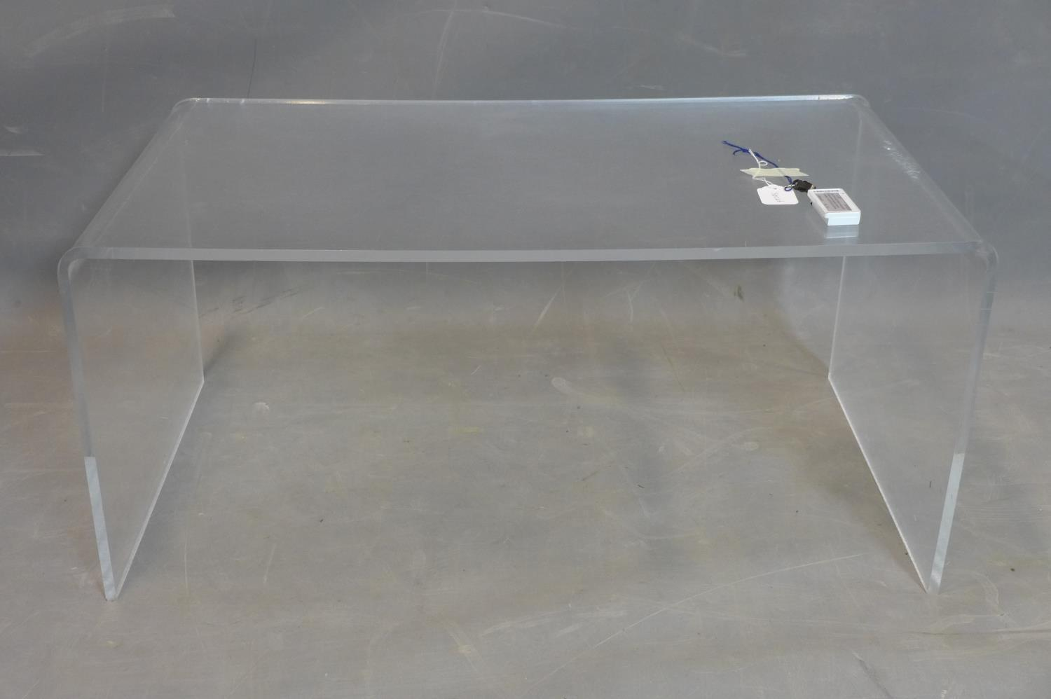 Lot 79 - A perspex table, H.40 W.90 D.50cm