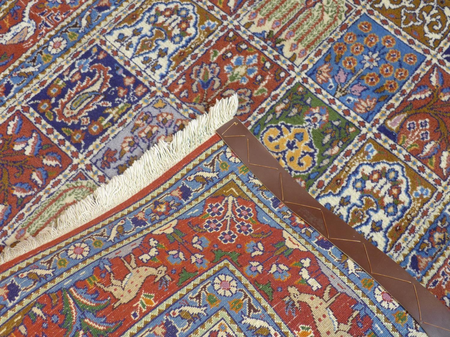 Lot 81 - A Persian rug with repeating tile design with stylised floral motifs, within border with flowers,
