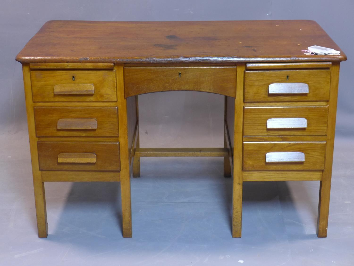 Lot 73 - An early 20th century oak desk, having six drawers flanking central short drawer, on square legs,