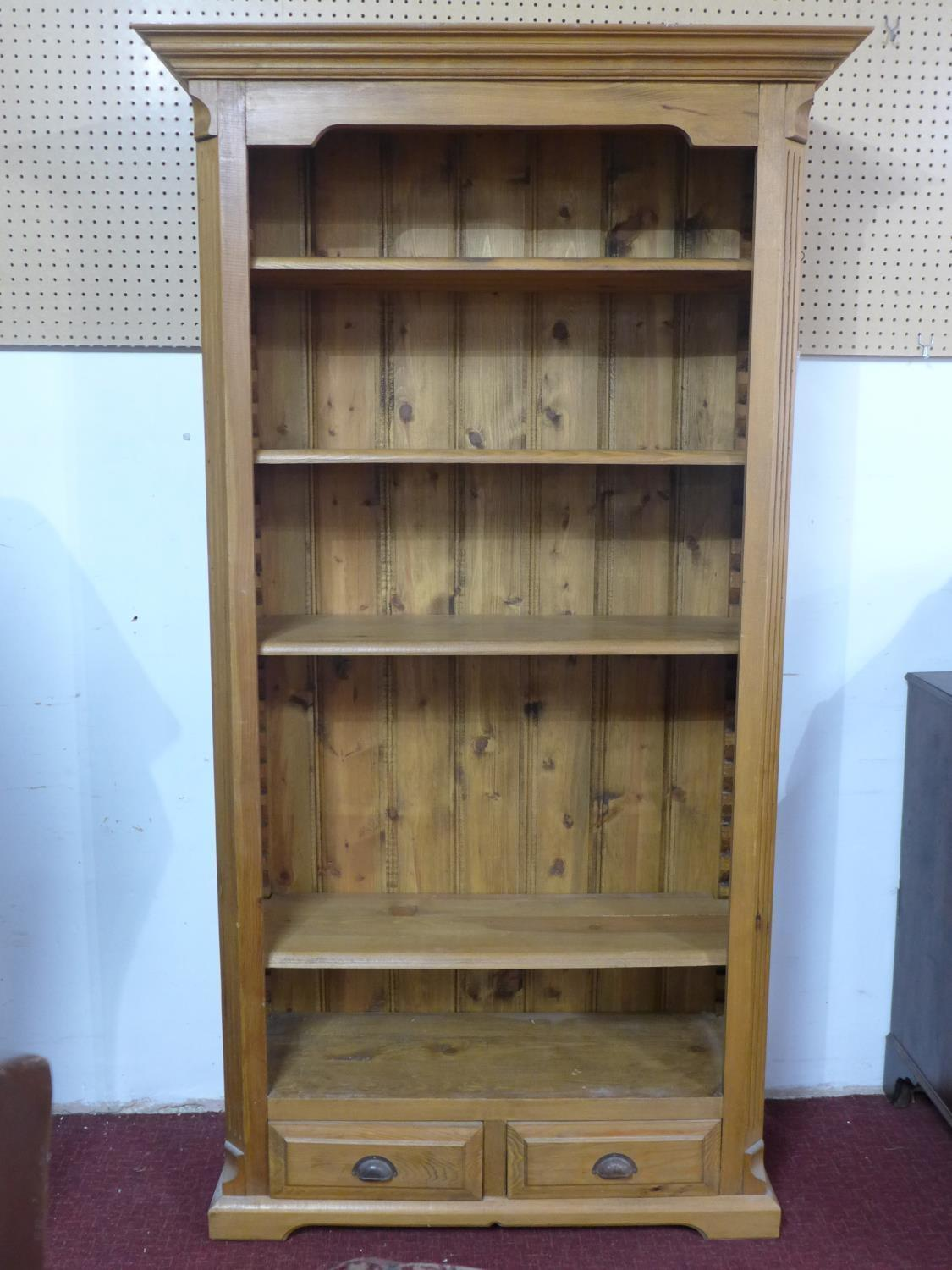 Lot 165 - A 20th century pine bookcase, having two small drawers, on bracket feet, H.198 W.107 D.38cm