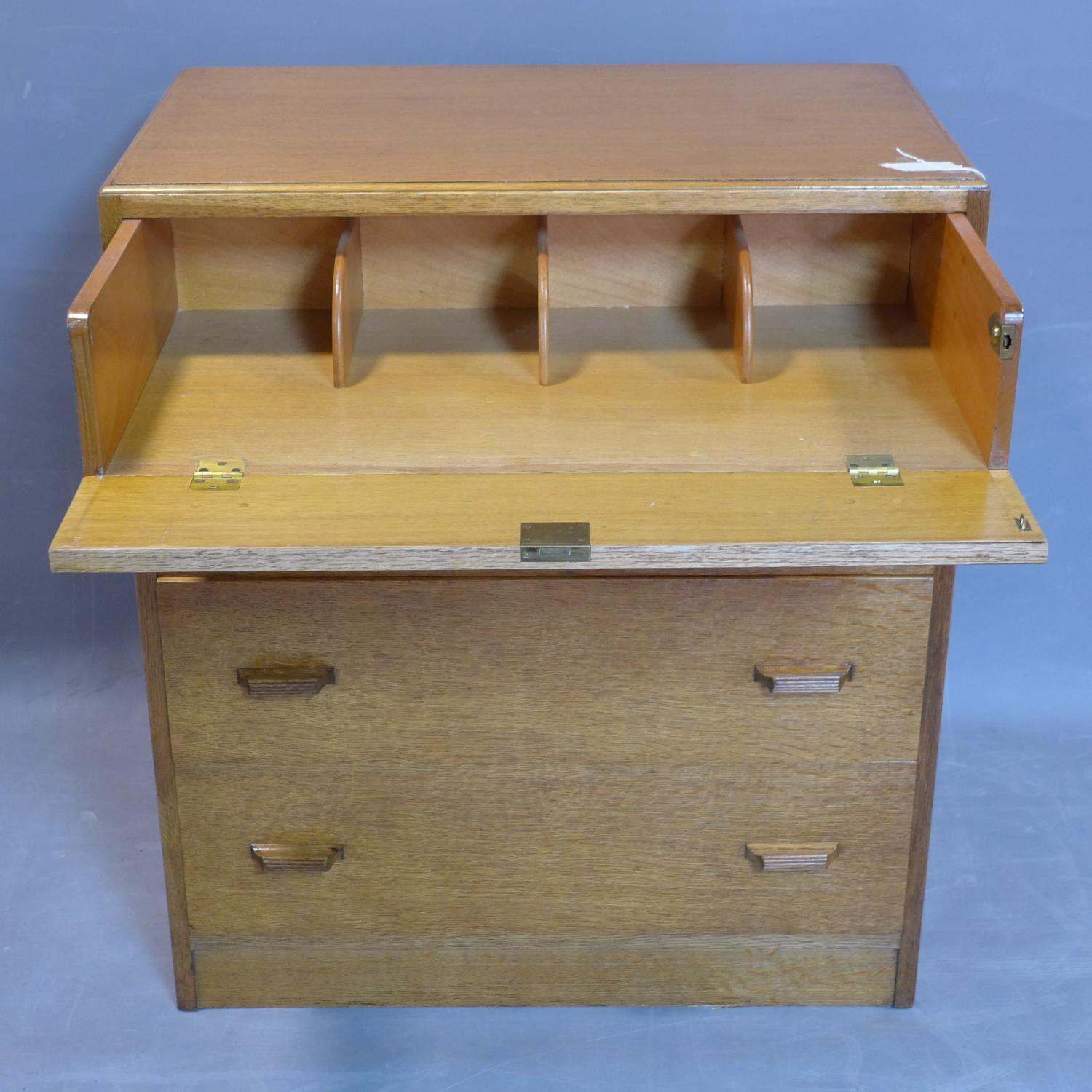 Lot 125 - An oak secretaire chest of drawers, with fitted secretaire having fitted interior above three long