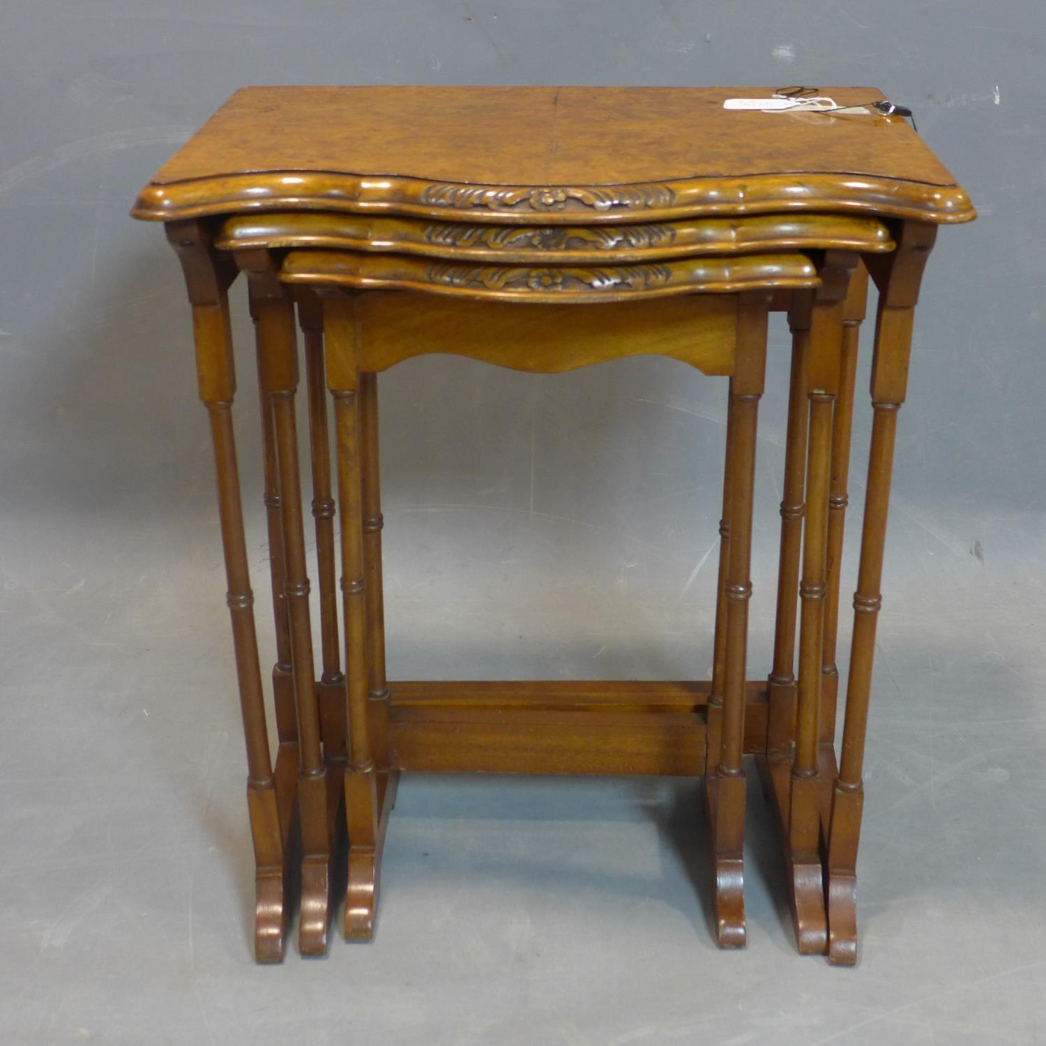 Lot 77 - A walnut nest of three tables, with quarter veneered tops with serpentine fronts, raised on
