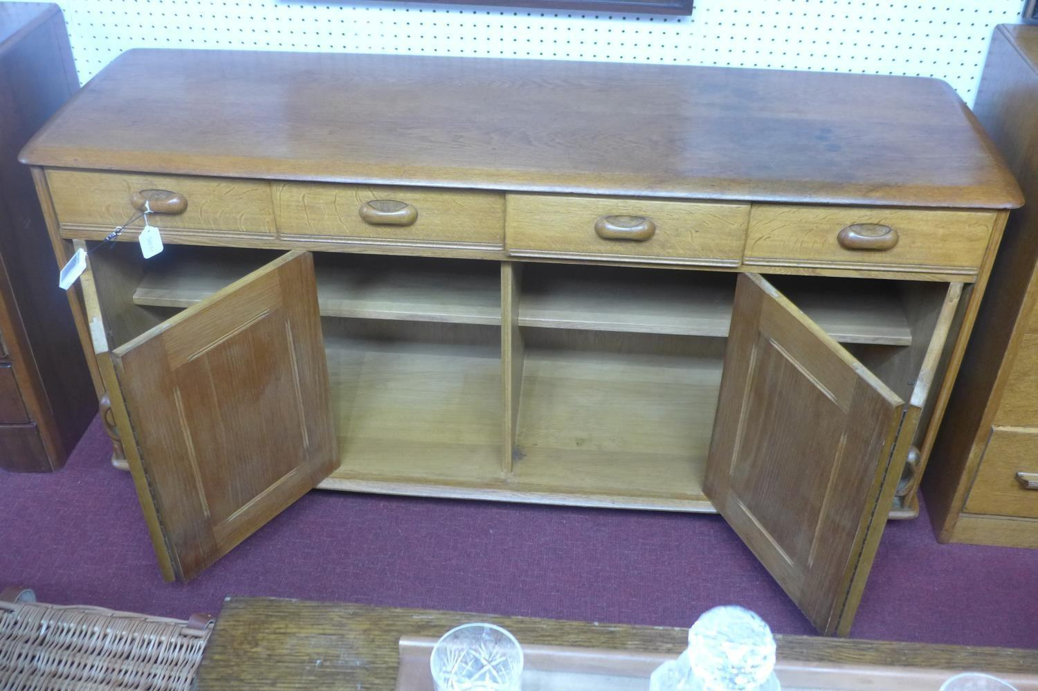Lot 84 - A mid 20th century Ercol teak sideboard, with four short drawers and two pairs of double doors, on