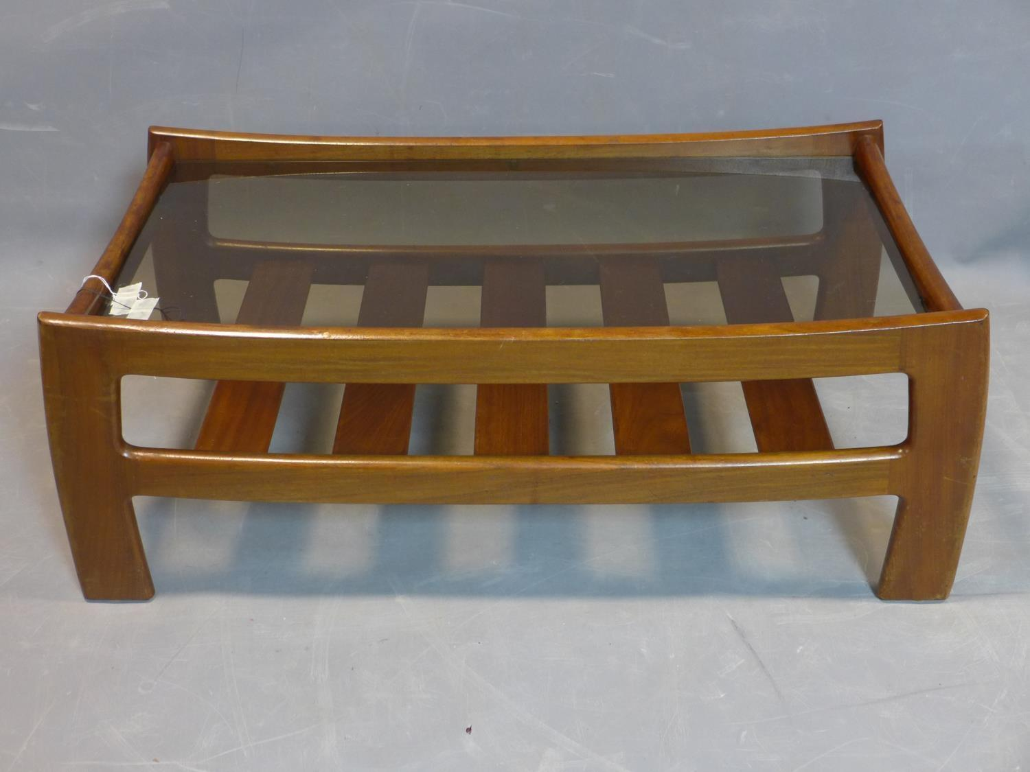 Lot 78 - A mid 20th century teak coffee table, with glass top above undertier rack, H.40 W.105 D.53cm
