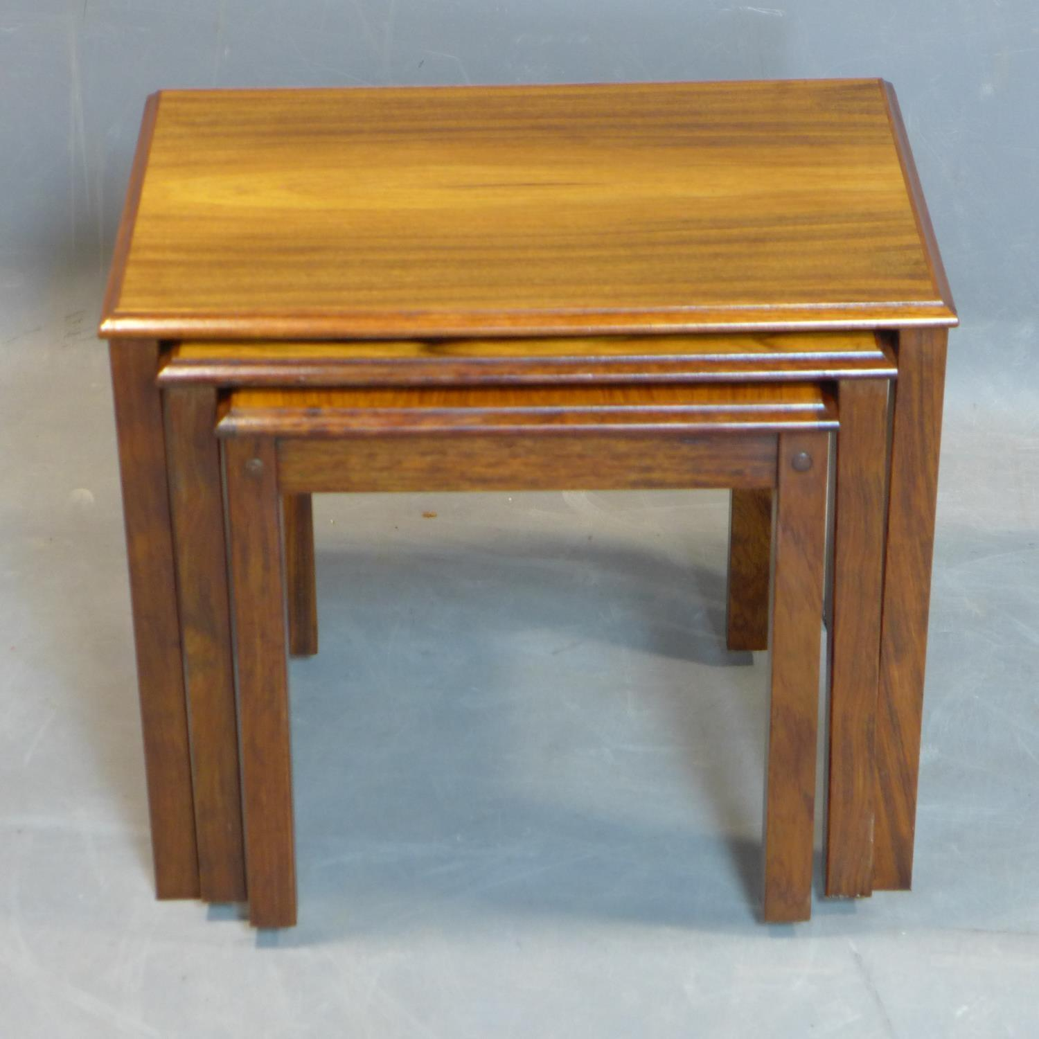 Lot 122 - A nest of three Danish exotic hardwood tables, marked 'Made in Denmark' to bases, H.46 W.54 D.39cm