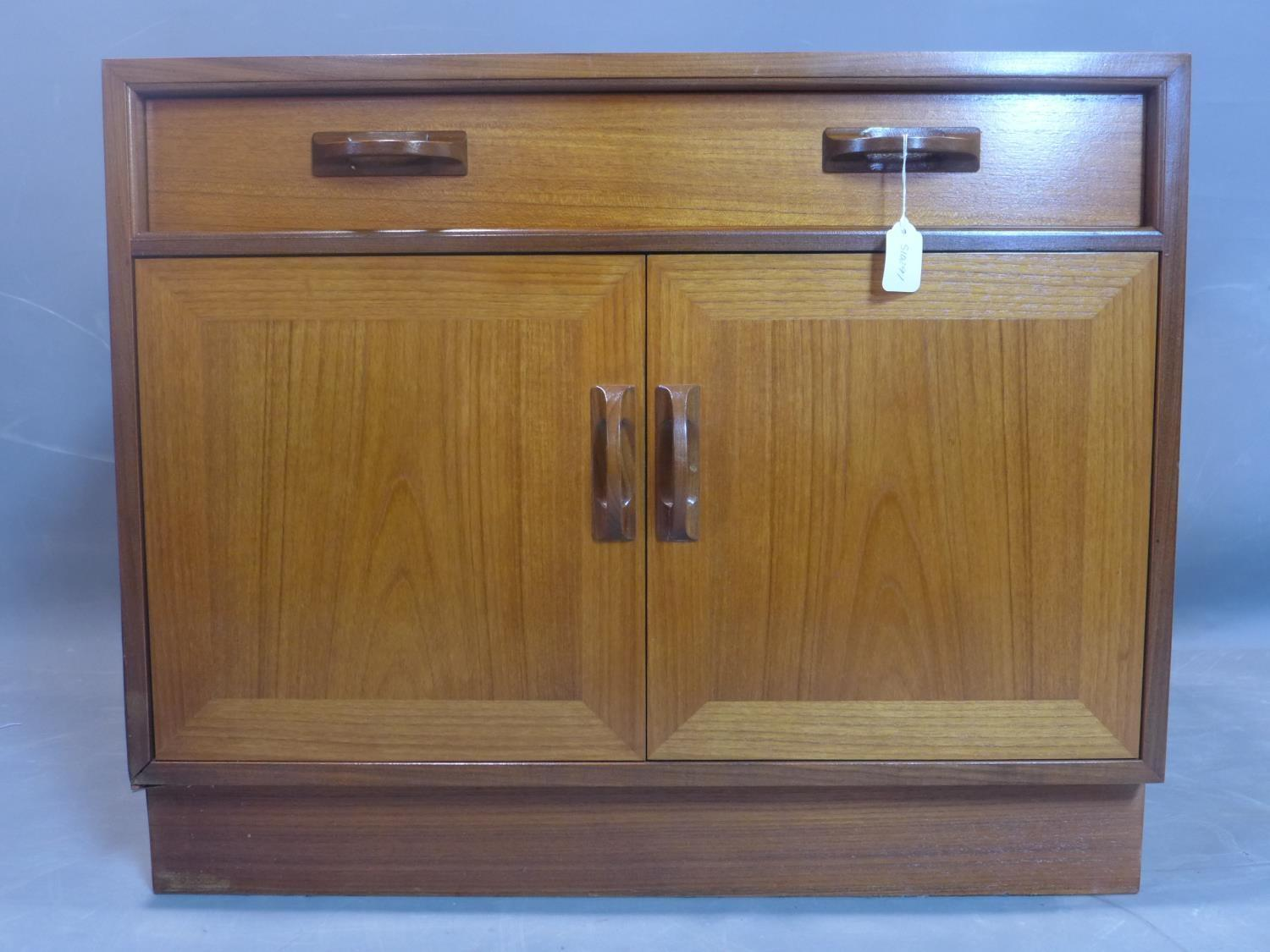 Lot 120 - A G-plan teak cabinet, with one long drawer above two cupboard doors, on pedestal base, label to